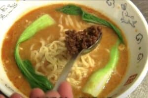 Top the noodles with minced pork and other toppings of choice