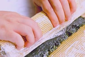 Roll the rice and toppings using bamboo mat