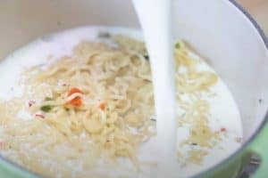 Add milk to the cooked noodles