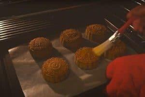 Brush egg wash on mooncake