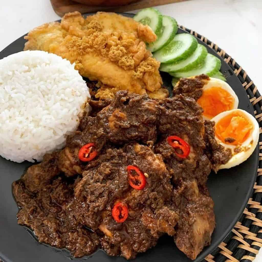 Chicken rendang served as a side dish with rice, eggs and vegetables