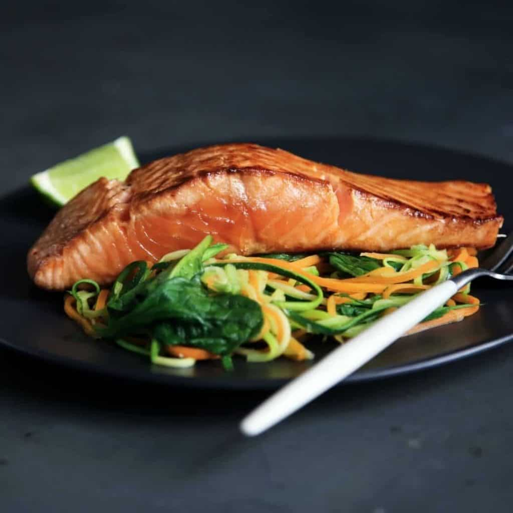 Cooked salmon over salad