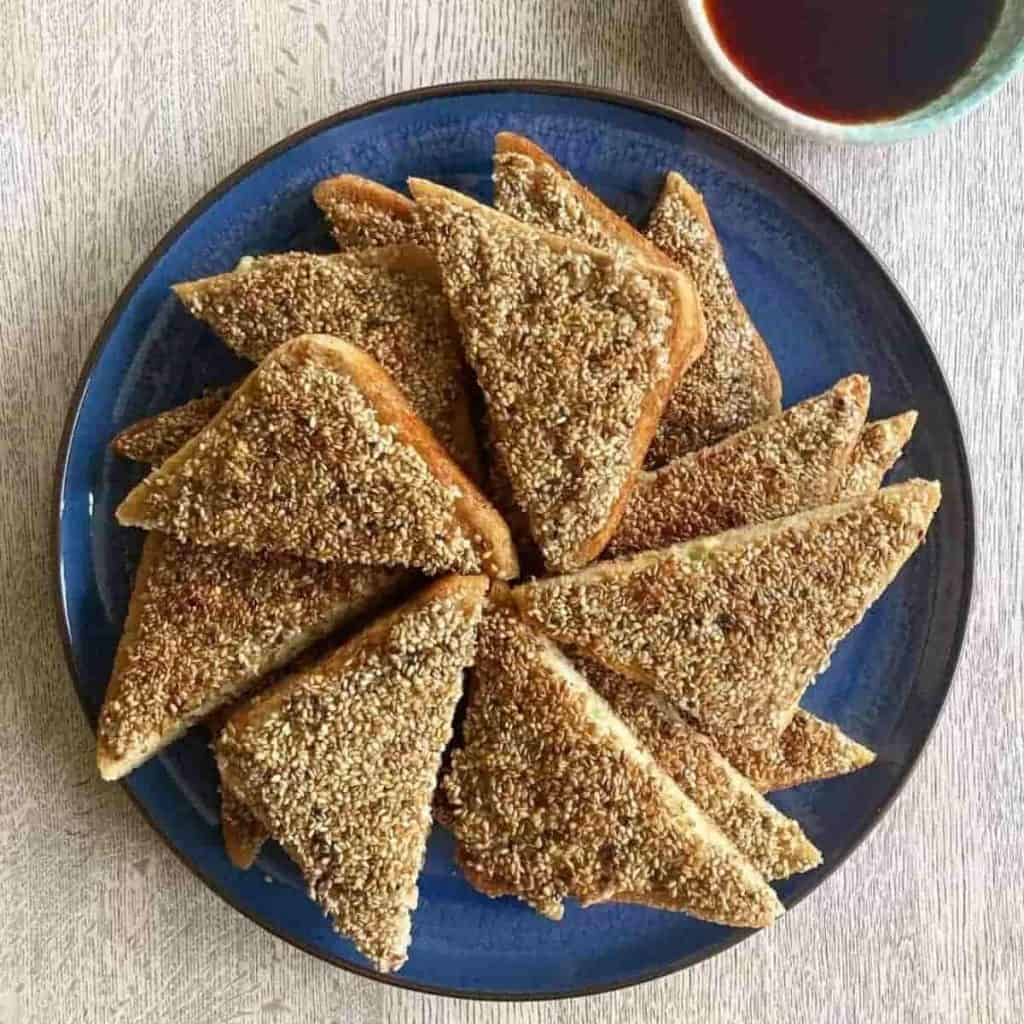 Prawn toast recipe sesame on blue plate with sauce on the side