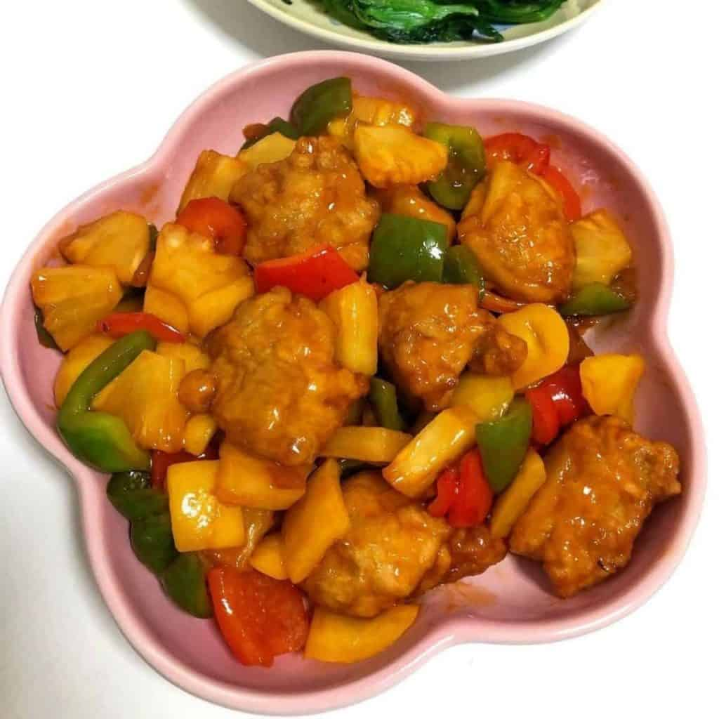 Sweet and sour chicken served with pineapples and peppers