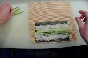 Place cucumber horizontally on rice