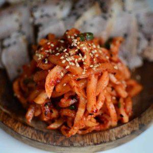 Moochae Musaengchae Radish kimchi with sesame seeds on wooden platter